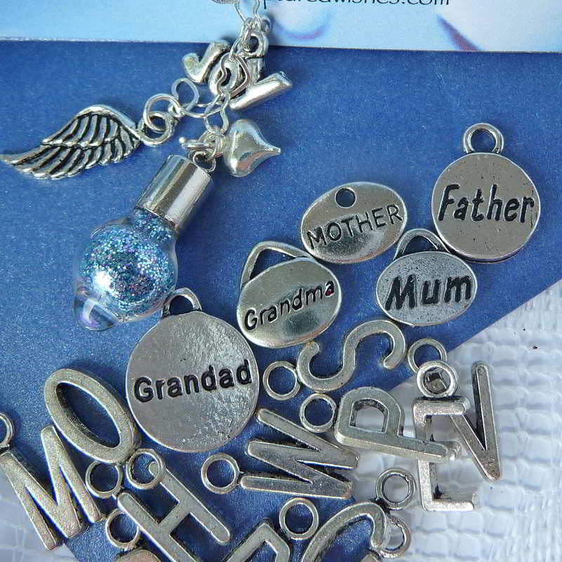 closeup of waterdrop wish vessel with samples of charms to use for personalilzation