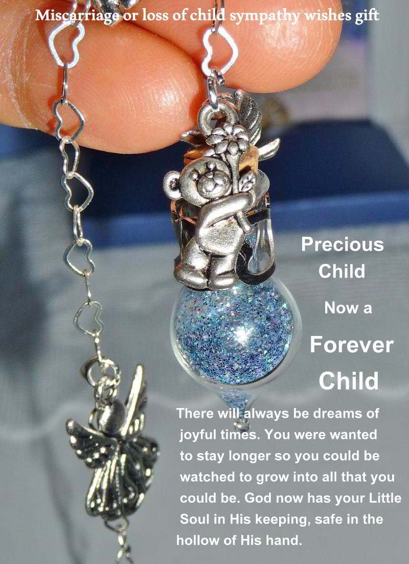 extreme closeup of Loss of Child Sympathy Tear vessel with a teddy bear and winged angel charms.
