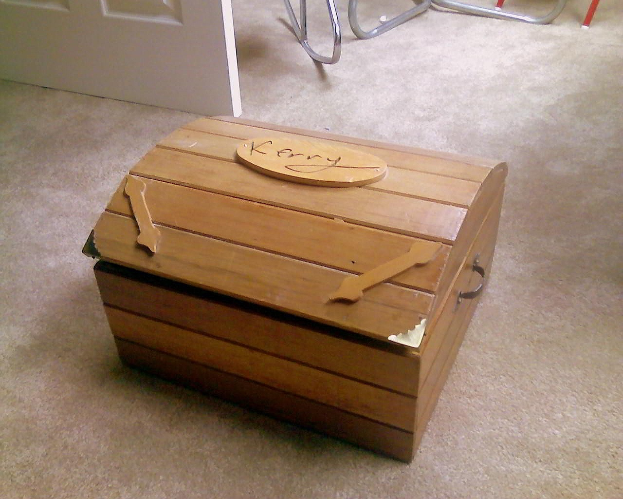 A memory box made of tan colored wood to hold memoirs of the deceased.
