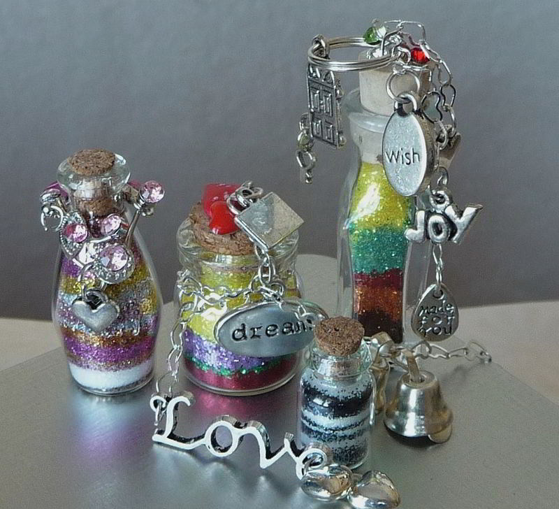 4 mini bottles with colorfully layered glitter with charms attached