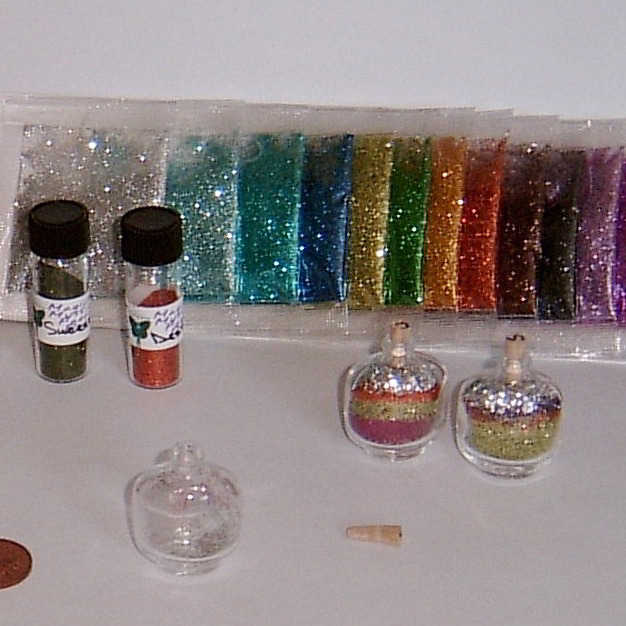 packages of different colored glitter behind empty miniature bottle