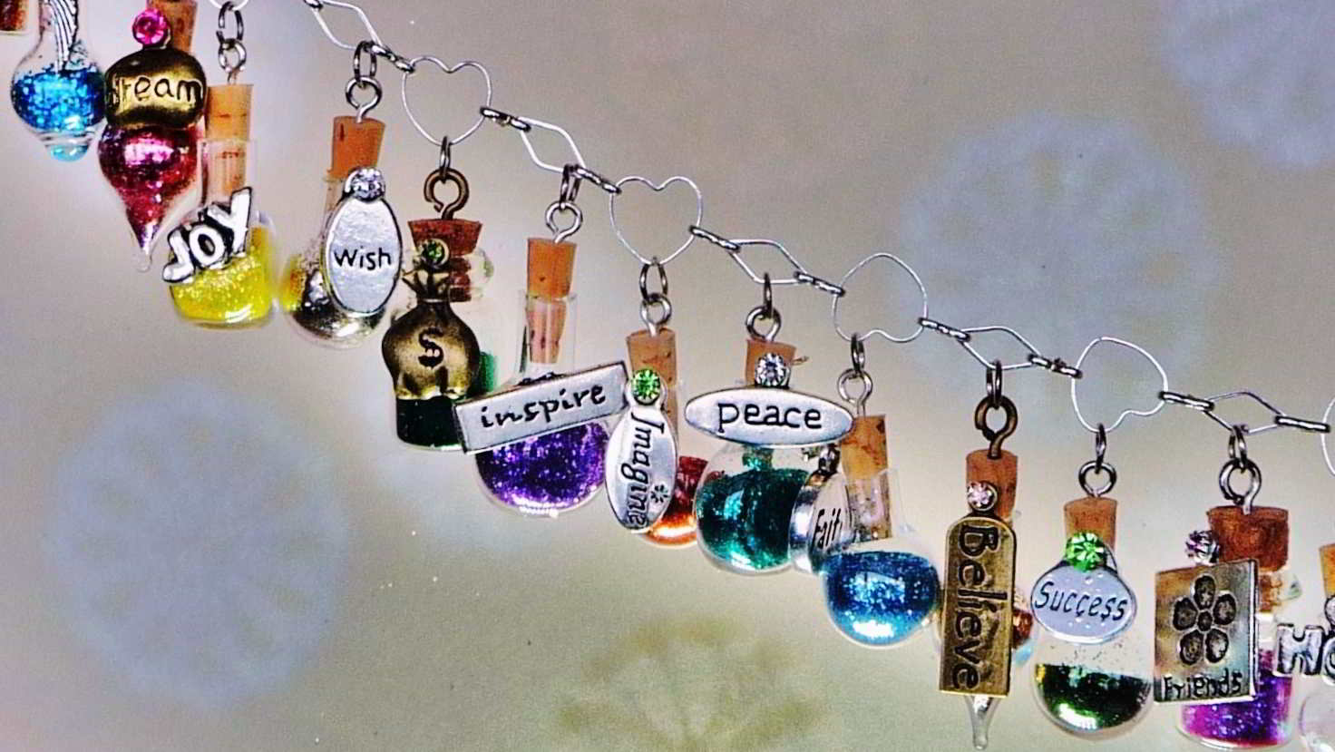 mini bottles filled with colorful glitter with meaning charms attached